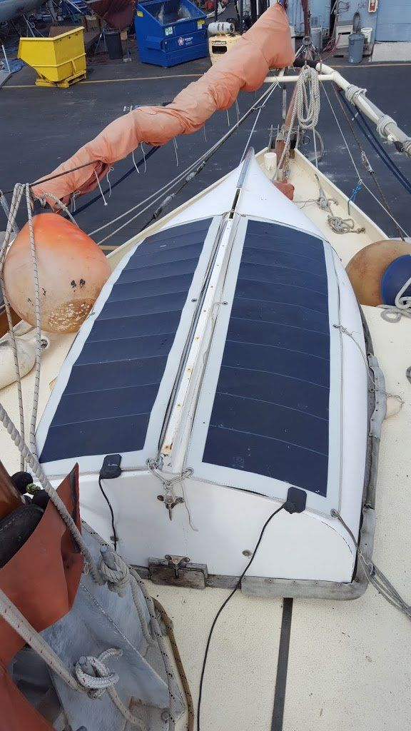 Two worn solar panels strapped to the top of an upside-down dinghy on the foredeck.