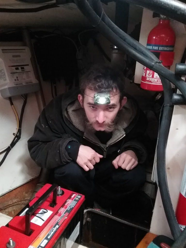 A man with a headlamp crouched in a quarterberth next to a large battery.