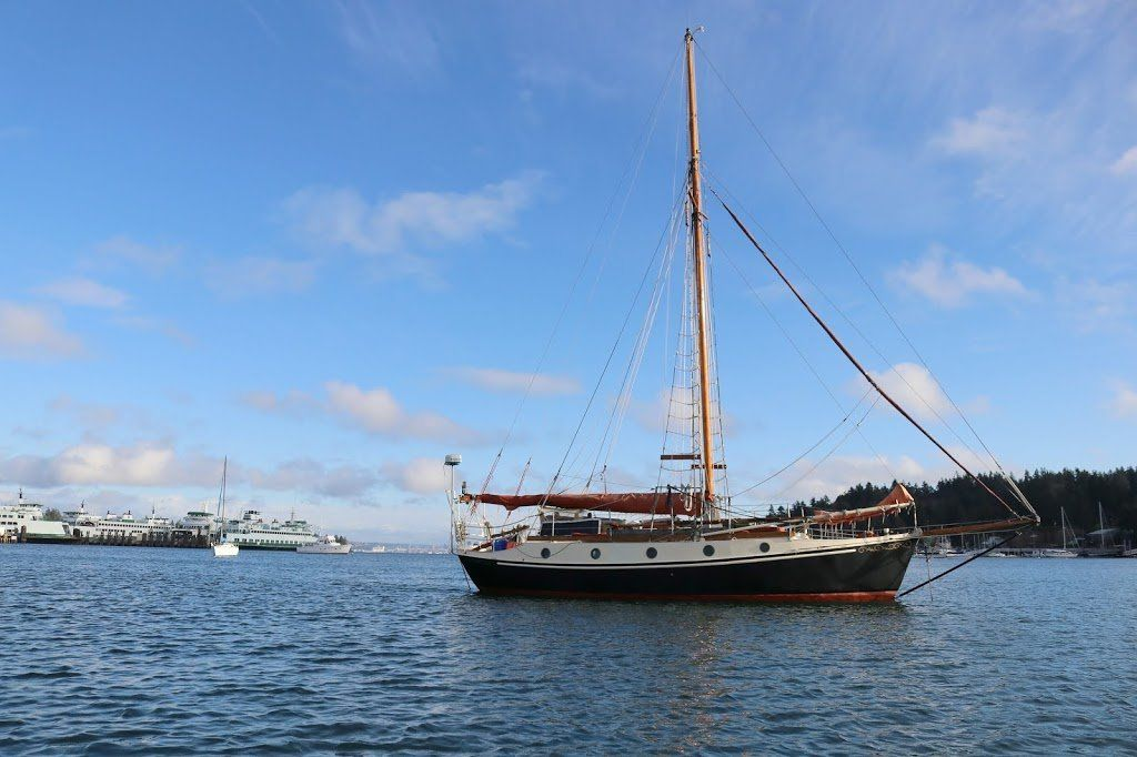 A sailboat at anchor on a mostly clear day. The boat has a black hull with white topsides and round portholes. The mast is wooden and the sails/sailcovers are rust colored.