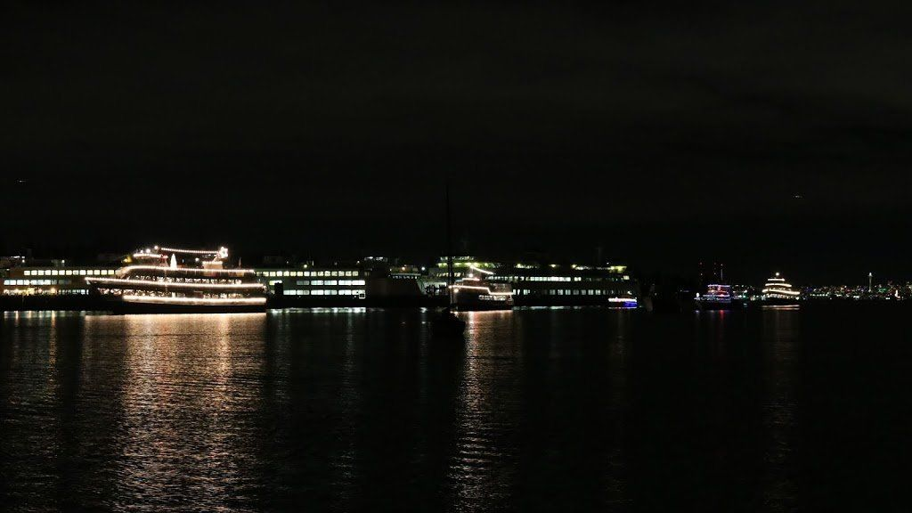 A night shot. There are several large boats lit with yellow lights creating reflections on the water.