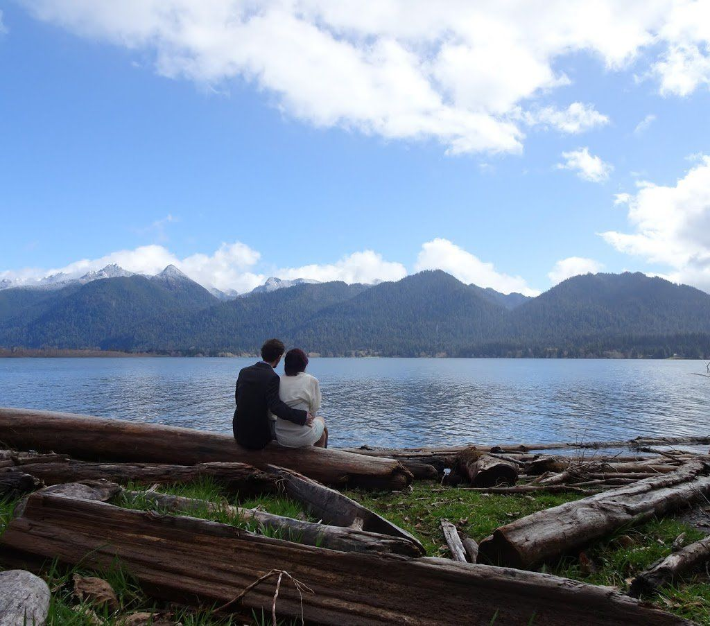 A couple sitting on a log in front of a beach with a lake and mountains in front of them.
