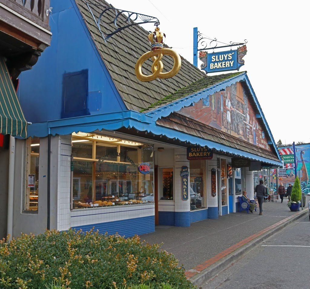 A blue and white bakery with a large golden kringle hanging from the sign. There is a mural on the gable of the building.