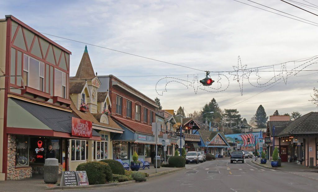 A view of a mainstreet. There are buildings with Scandinavian features and some holiday decorations.
