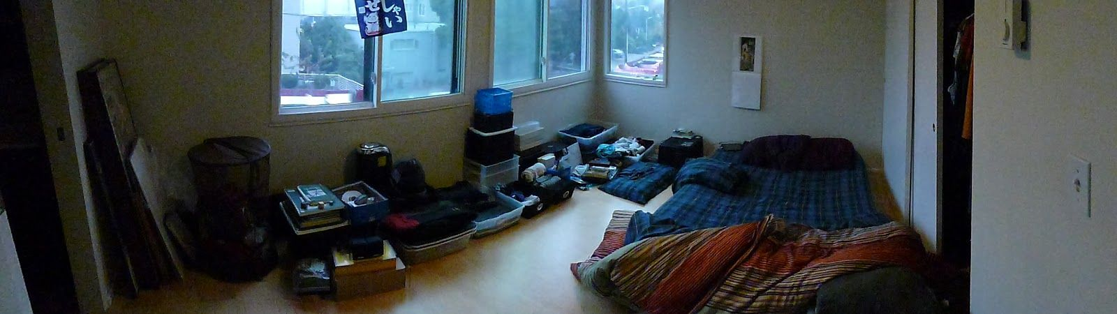 A room with a bed on the floor and a relatively small collection of belongings.