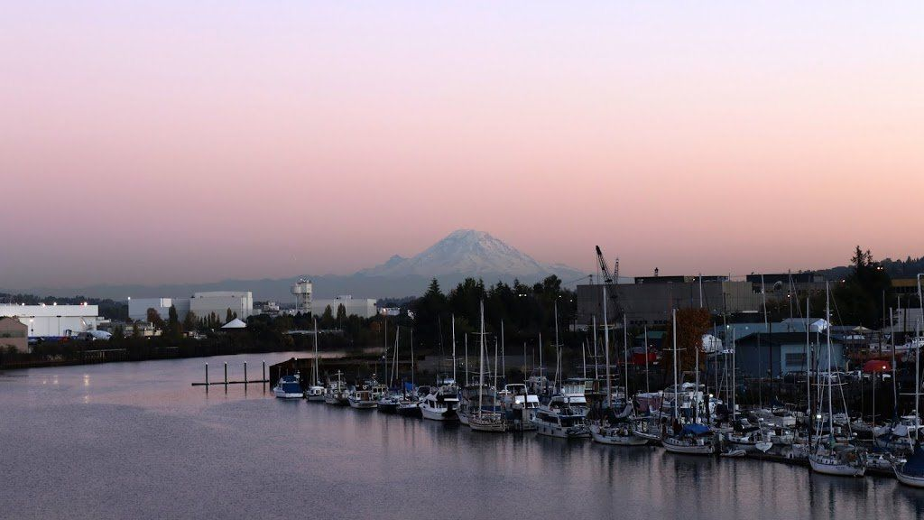 A riverbank with a small but crowded marina. It is dusk and Mount Rainier is visible in the background.