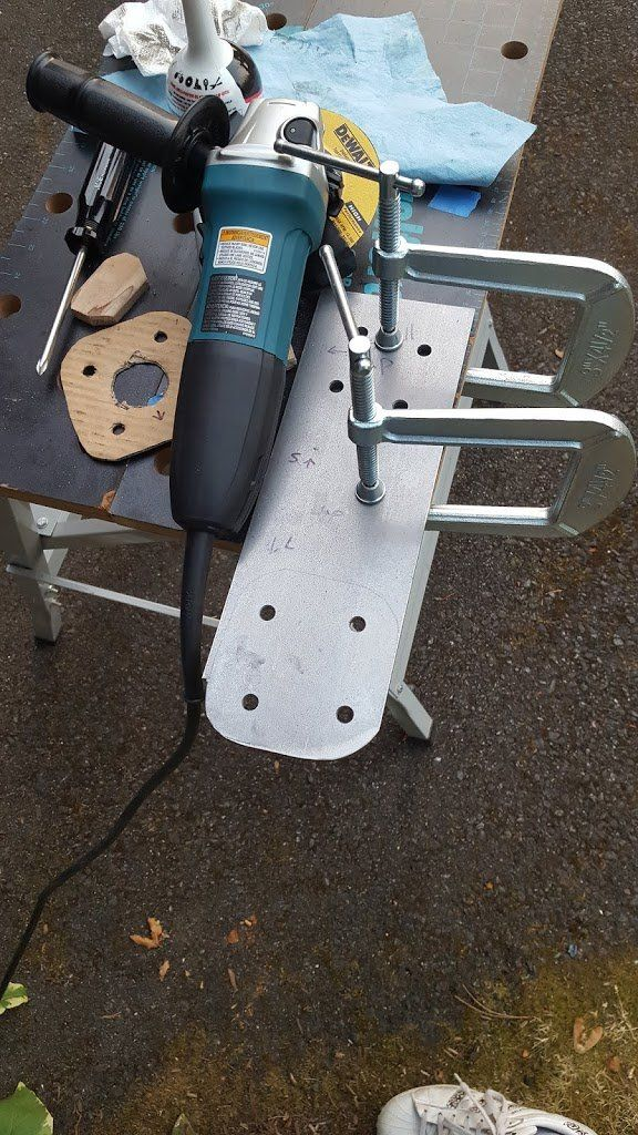 A piece of steel clamped to a table. There are some drilled holes and drawn lines. An angle grinder is sitting next to to it.