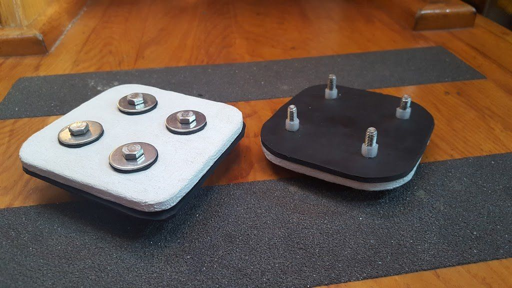 Two assemblies of painted metal plates, rubber, and bolts with washers and spacers.
