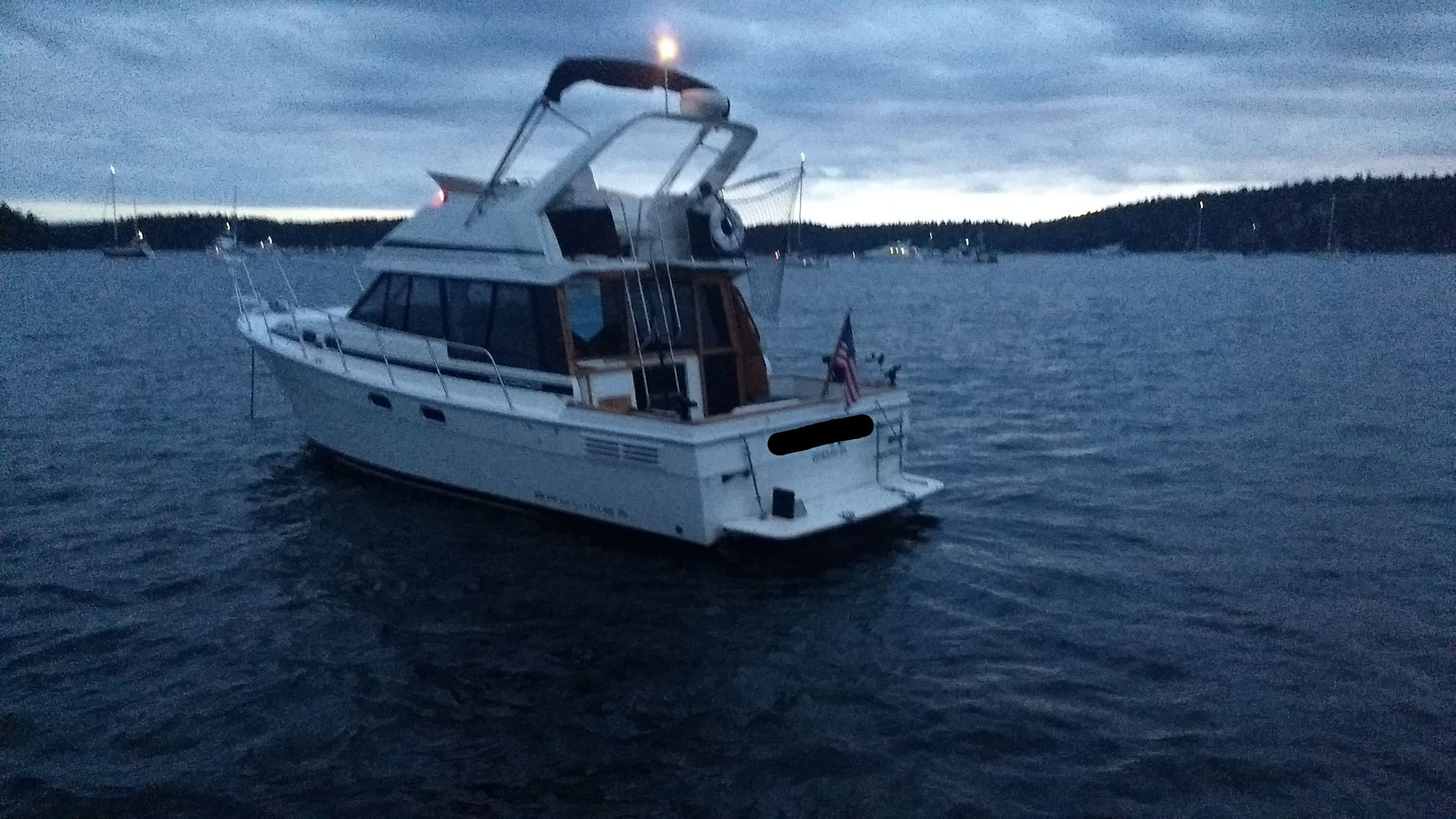 A medium-sized white power boat at dusk with its anchor light on.