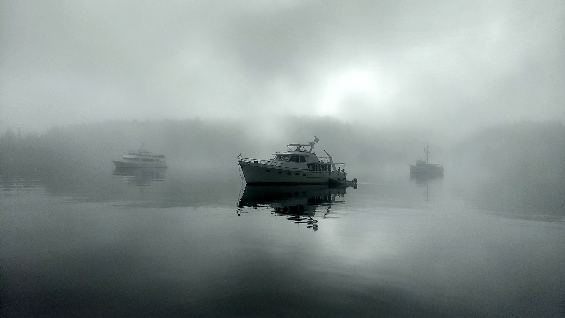 Three boats in brightly-lit dense fog. One is close enough to be crisply detailed.