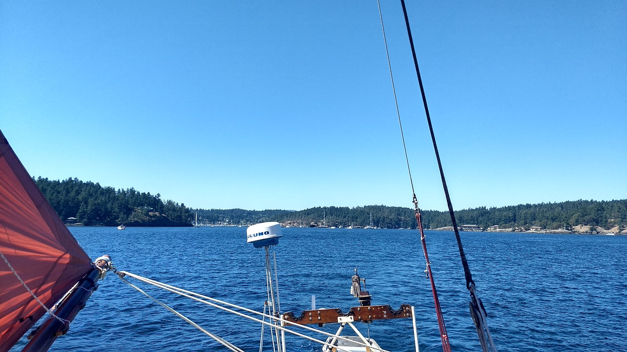 A view from the stern of a sailboat. An anchorage with many boats is visible in the distance.