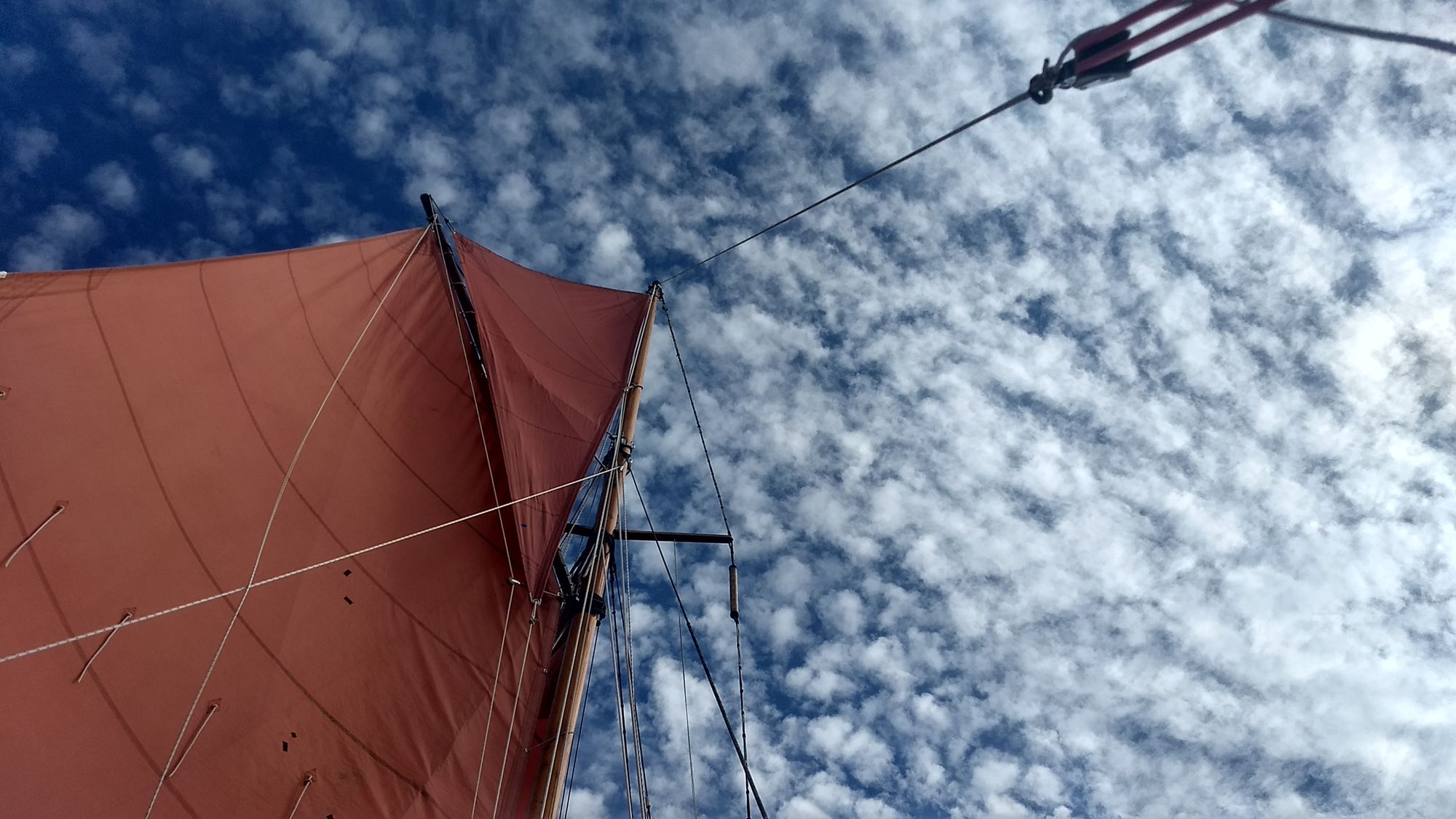 Looking up the mast at the topsail. The sky is dappled with fluffy white clouds.