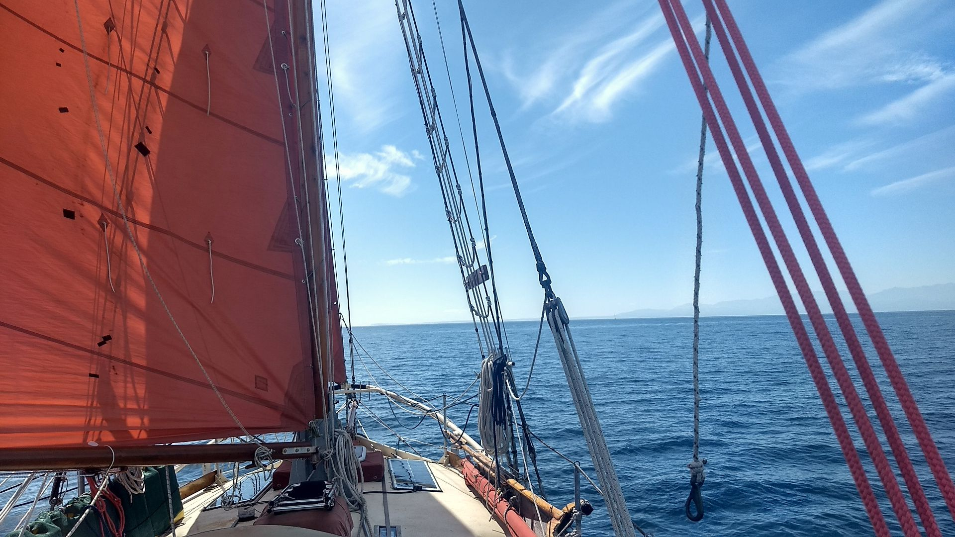 A view from the cockpit. A rust-colored sail fills the left-third of the image. Lines and rigging cross the right side. The water is calm and the sky is blue with wispy clouds.