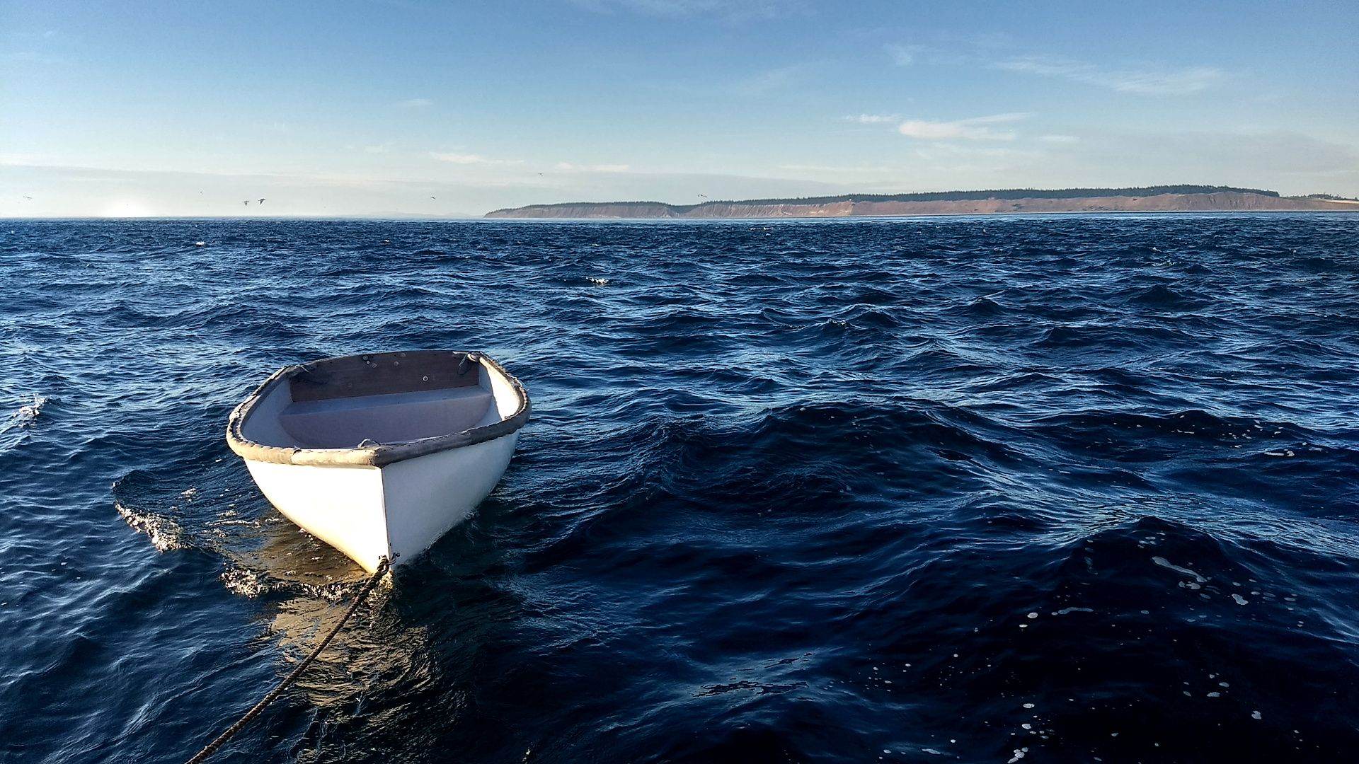 A small dinghy bouncing through some rough water.