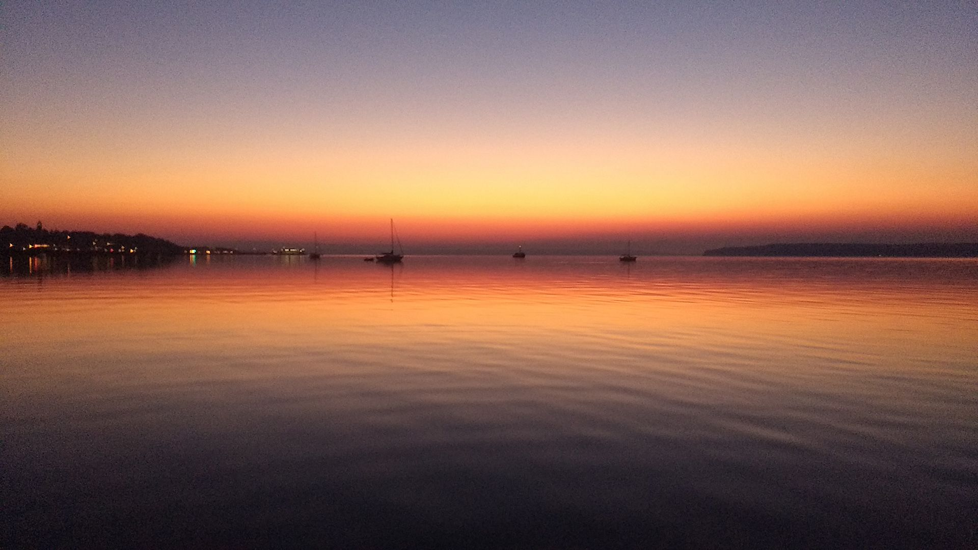 A sunrise with a very dark, saturated orange-purple horizon reflected on the water.