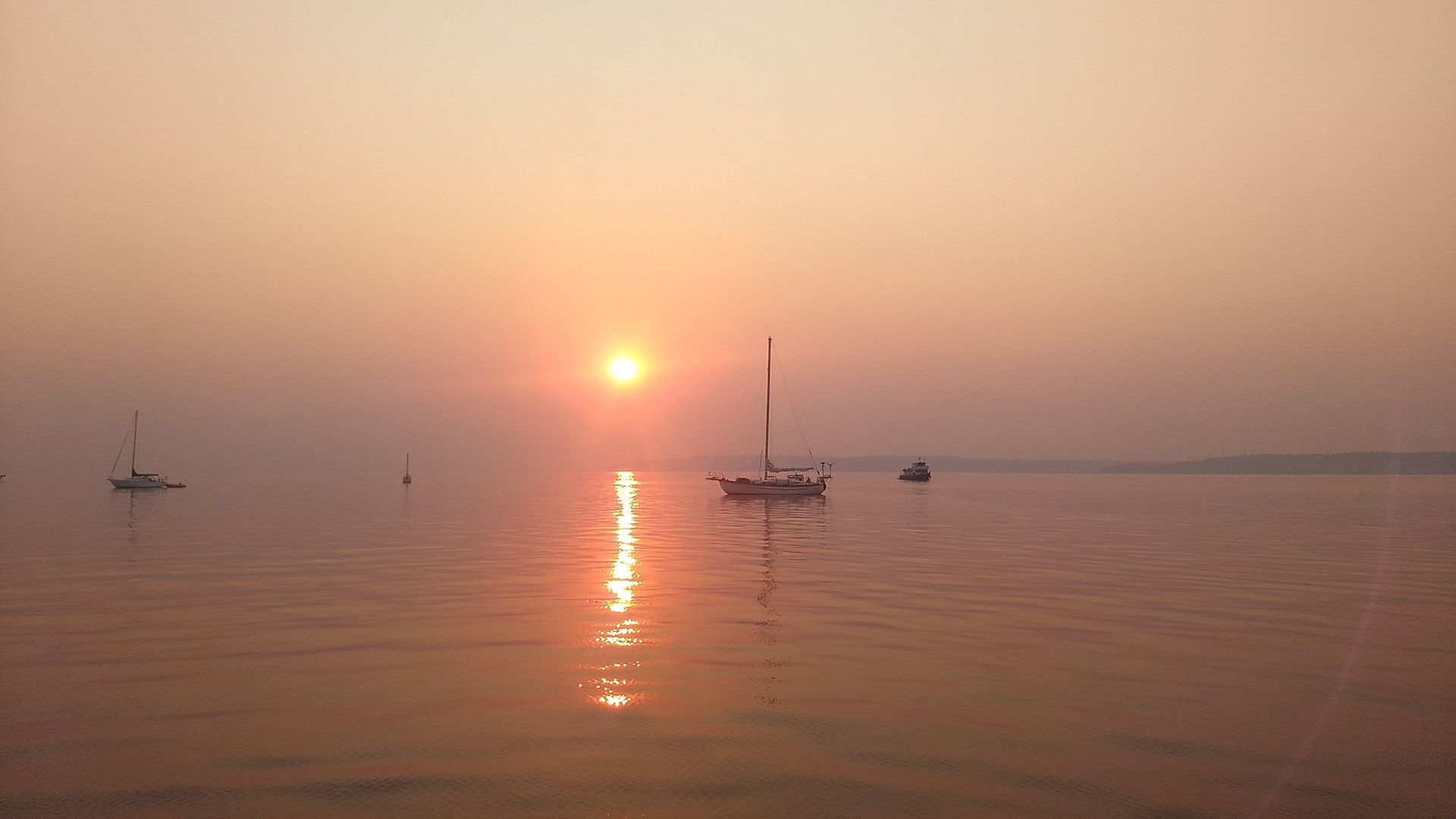 Several boats at anchor with a red, hazy sunrise in the background.