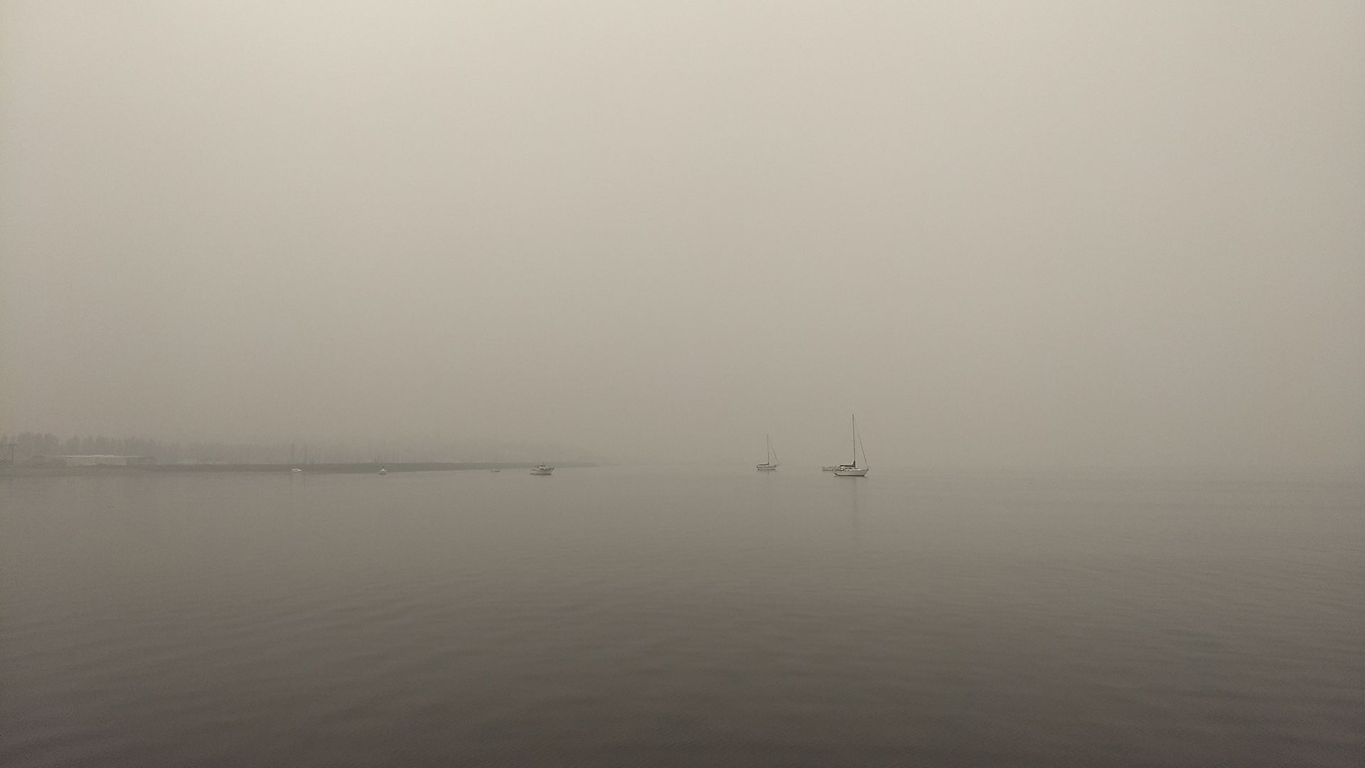 Some boats visible. The sky and water are gray. The shore is barely visible.