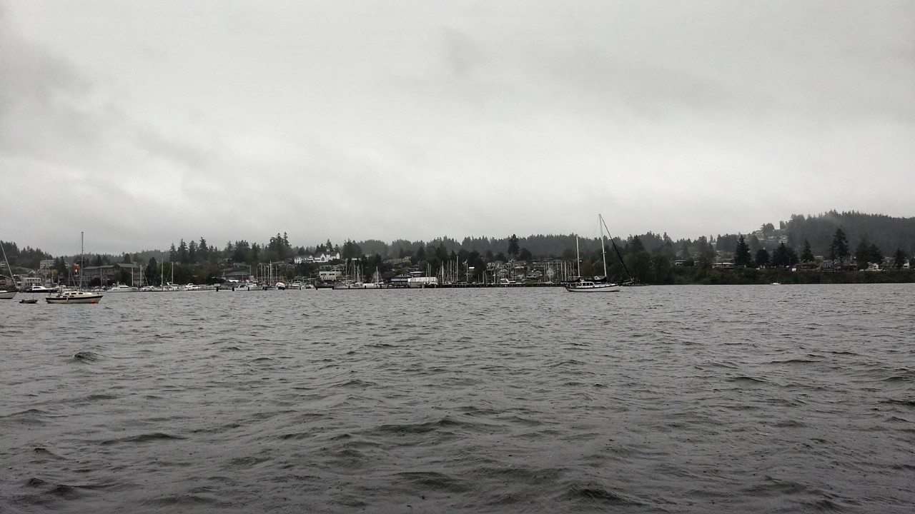 Gray skies and choppy weather over a bay with a few boats at anchor.