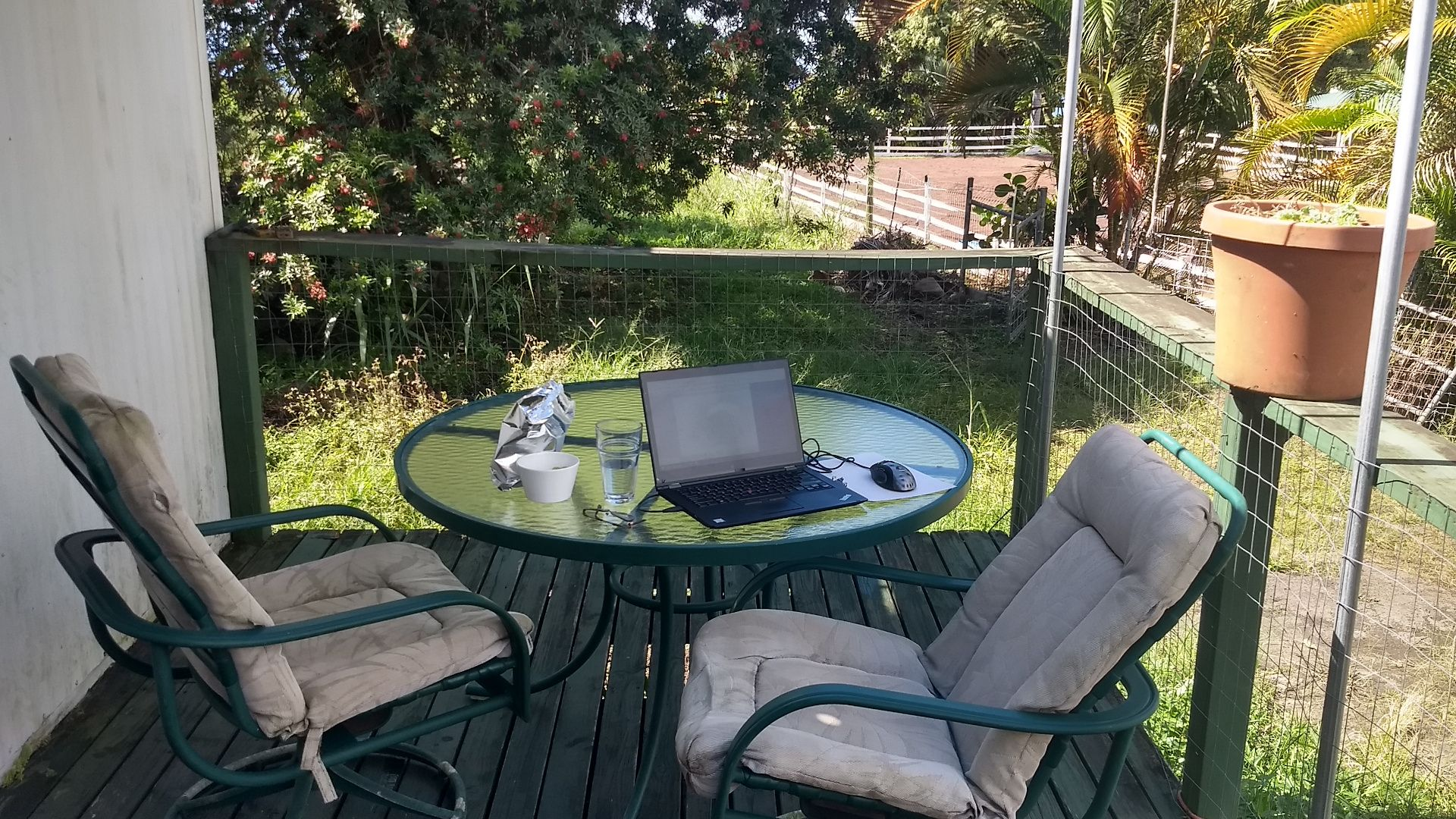 A laptop on a glass patio table.