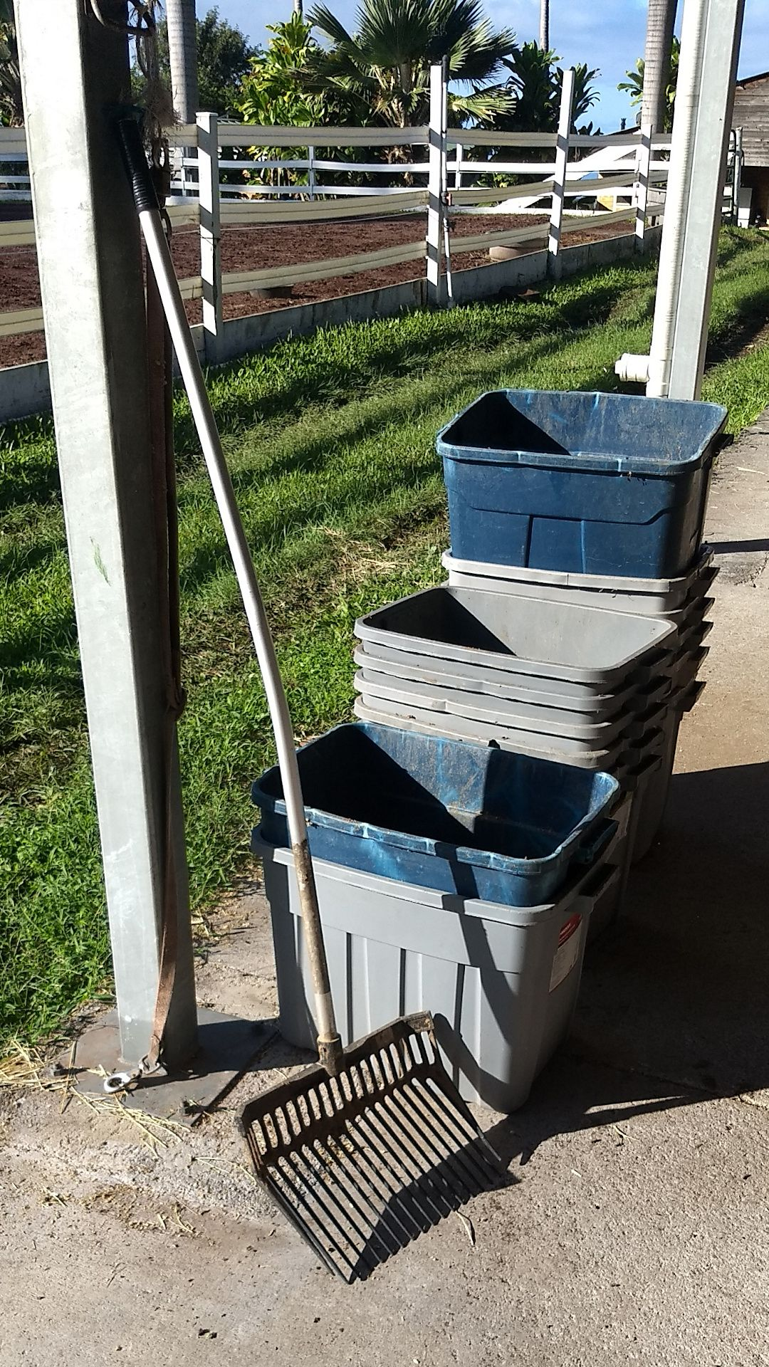 A manure fork in front of a stack of muck buckets.